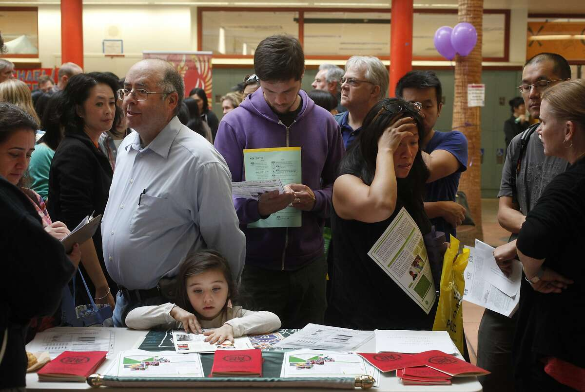 From left, Dina Bakour and Said Nuseiben talk with a representative of Alice Fong Yu Alternative School as Nuseiben's daughter Kindah Nuseibeh examines pamphlets while Brendan VanderMei, center, and Lily Tung Crystal, right, look over and discuss details at the SFUSD school enrollment fair at John O'Connell High School Oct. 25, 2014 in San Francisco, Calif.