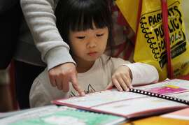 Ashley Li, 4, looks at a book on display as her mother Sichen Liu chats with Chinese Immersion school representatives at the SFUSD school enrollment fair at John O'Connell High School Oct. 25, 2014 in San Francisco, Calif.