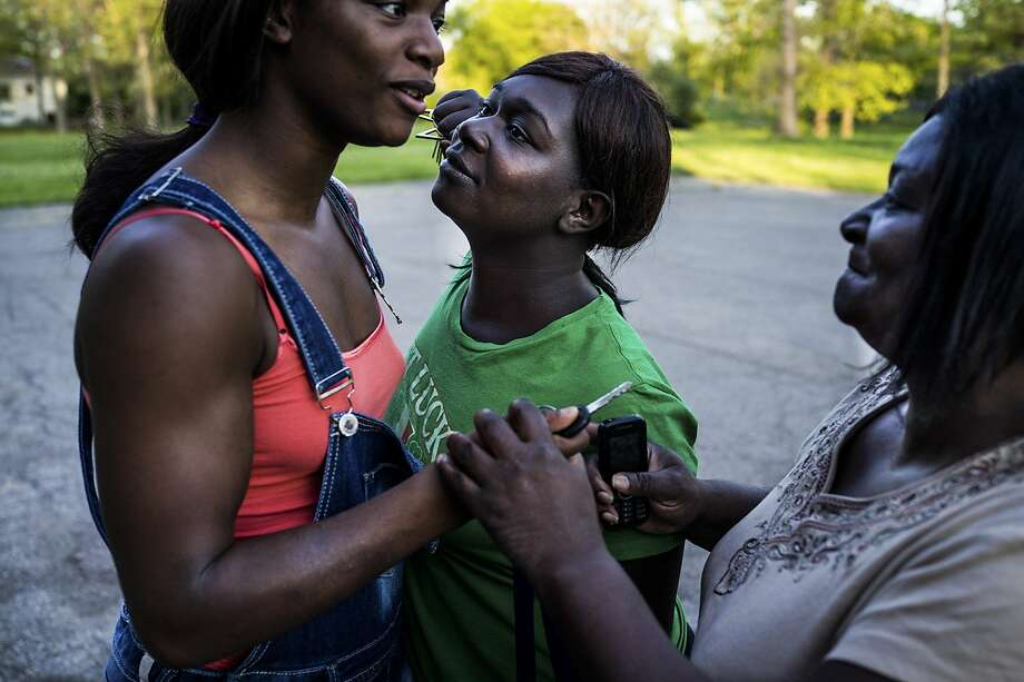 "Olympic Gold Medal Boxer Claressa ""T-Rex"" Shields (right) and her sister Brianna play-fight while their mother, Marcella, tries to get in between them. Flint, Mich. May 2014. Photo: Zackary Canepari"
