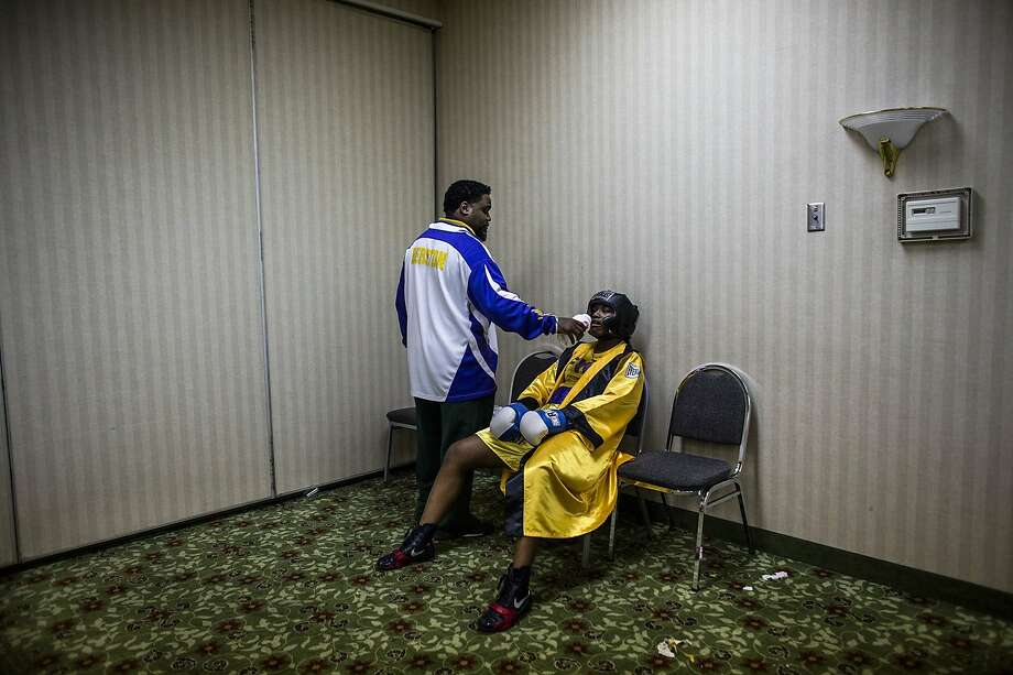 Coach Jason Crutchfield gives his fighter, Claressa Shields, a little water before she goes into the ring against former Canadian champion Mary Spencer. Photo: Zackary Canepari