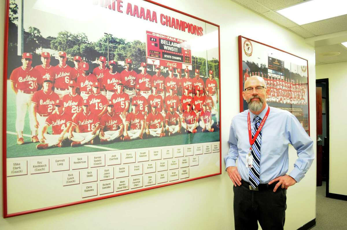 Bellaire High School Principal Michael McDonough stand in front of the Bellaire Baseball Championship team photos.