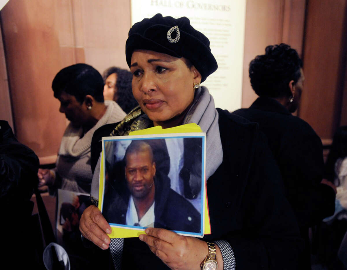 Hawa Bah, mother of Mohamed Bah, holds a photo of her late son at a news conference at the Capitol in Albany, N.Y., on Tuesday, April 28, 2015. Families of civilians killed by police officers are urging New York Gov. Andrew Cuomo to issue an executive order calling for special prosecutors in those cases. (AP Photo/Tim Roske)
