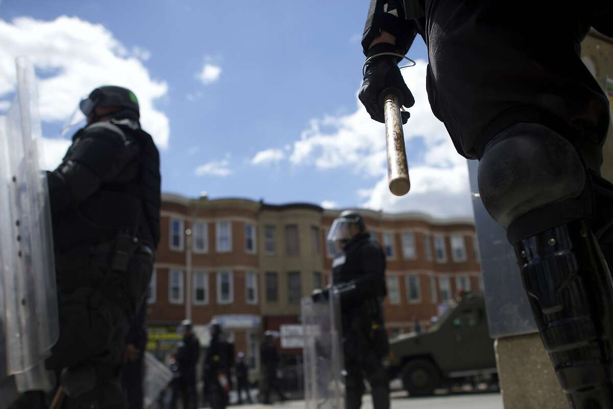 Baltimore police in riot gear patrol the streets in a neighborhood where rioters burned a CVS pharmacy Monday. The governor sent National Guard troops and State Police troopers into the city.