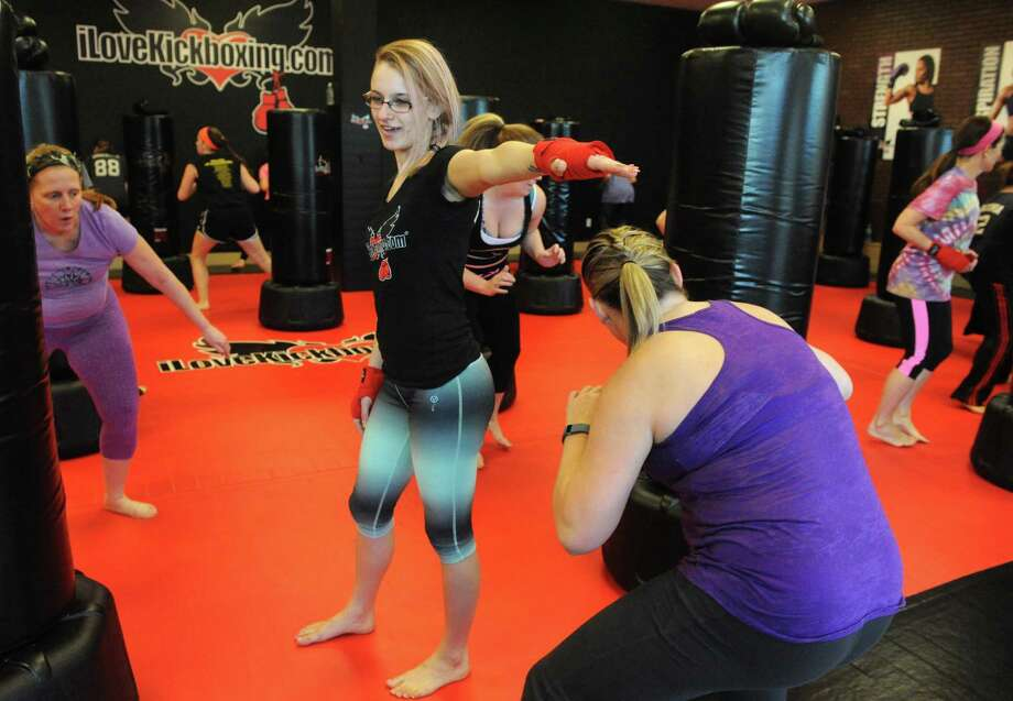 Instructor Kathy Scheffler gets her students warmed up during a class at iLoveKickboxing.com in the Clifton Park Center Mall on Wednesday March 18, 2015 in Clifton Park, N.Y.  (Michael P. Farrell/Times Union) Photo: Michael P. Farrell / 00031067A