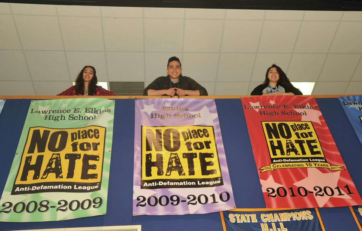 Afra Asadi, left, Edgar Villafane and Linda Li stand above the No Time for Hate banners displayed in the entryway of Elkins High School.