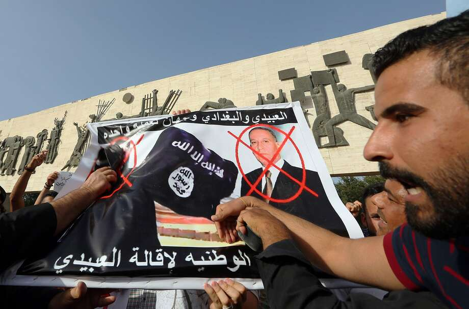 """Protesters carry defaced posters of Islamic state leader Abu Bakr al-Baghdadi, left, and Iraqi Defence Minister Khaled al-Obeidi, right, as they chant slogans against the Islamic State group during a protest at Tahrir Square in Baghdad, Iraq, Monday, April 27, 2015. The banner reads in Arabic: """"Obeidi and Baghdadi two sides of one coin."""" Security forces struggle to dislodge the Islamic State group from vast areas in northern and western Iraq seized by the extremists during a stunning blitz last summer. Photo: Hadi Mizban, Associated Press"""