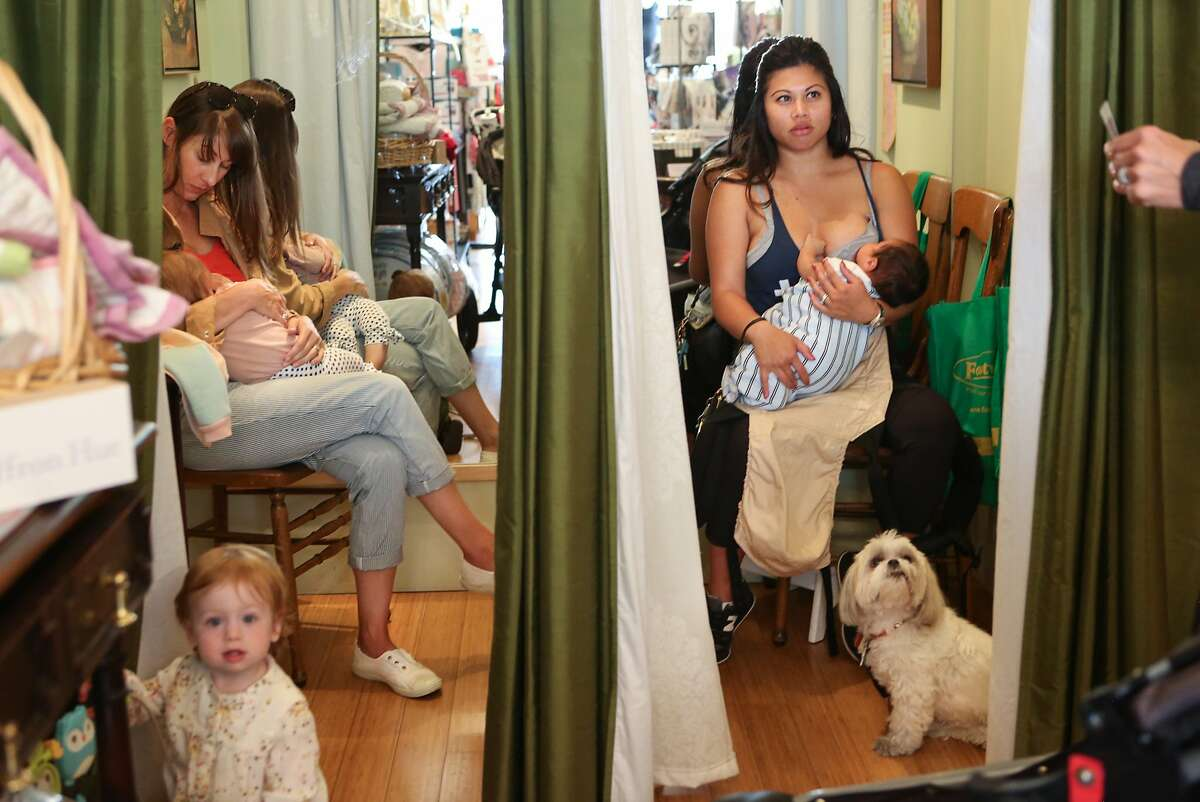 Left to right -- Taking advantage of the feeding rooms, Theresa McNulty breastfeeds 8 month old daughter, Ivy, and chats with new mom Jennifer Barulich who also feeds her 5 week old son, Jacob while another baby, 15 month old Brynn Waldman, plays nearby at Burlingame Breastfeeding Center in Burlingame, Calif., on Tuesday, April 28, 2015.