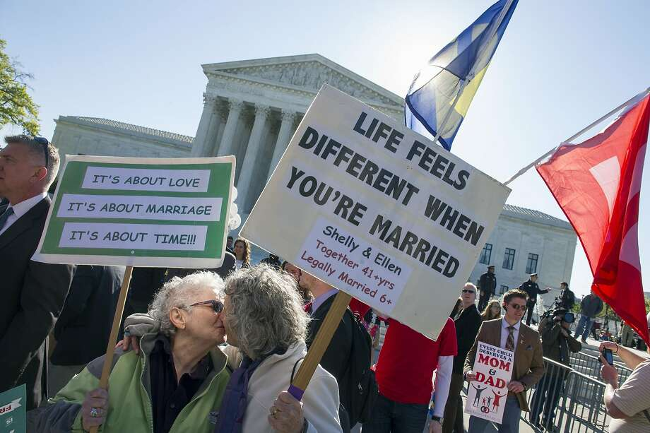 Shelly Bailes, 74, left, and her wife, Ellen Pontac, 73, both of Davis, Calif., kiss in front of the Supreme Court in Washington, Tuesday, April 28, 2015. The Supreme Court is set to hear historic arguments in cases that could make same-sex marriage the law of the land. The justices are meeting to offer the first public indication of where they stand in the dispute over whether states can continue defining marriage as the union of a man and a woman, or whether the Constitution gives gay and lesbian couples the right to marry. (AP Photo/Cliff Owen) Photo: Cliff Owen, Associated Press