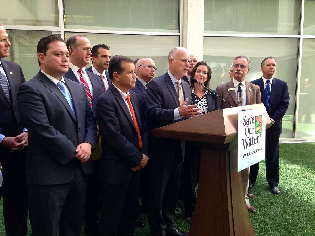 Gov. Jerry Brown is surrounded by big-city mayors, including Oakland Mayor Libby Schaaf, on April 28, 2015 as he announces legislation at the Capitol to help cities and local agencies crack down on water wasters.