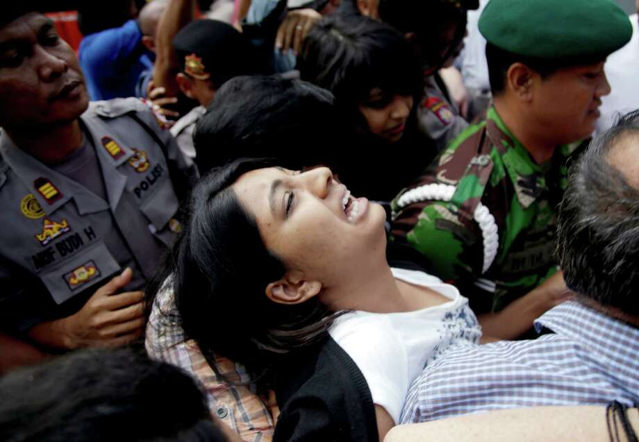 Brintha Sukumaran, center, sisters of Myuran Sukumaran, an Australian on death row, cries upon arrival at Wijayapura ferry port to cross to the prison island of Nusakambangan, in Cilacap, Central Java, Indonesia, Tuesday, April 28, 2015. Indonesia notified nine foreigners and a local man convicted of drug trafficking over the weekend that their executions will be carried out within days, ignoring appeals by the U.N. chief and foreign leaders to spare them. (AP Photo/Tatan Syuflana) Photo: Tatan Syuflana, STF / AP