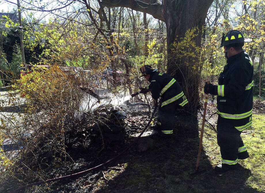 Firefighters at the scene of a brush fire that burned a wooded area at Ferry Lane East and Manitou Road on Tuesday afternoon. Photo: Westport Fire Department / Westport News