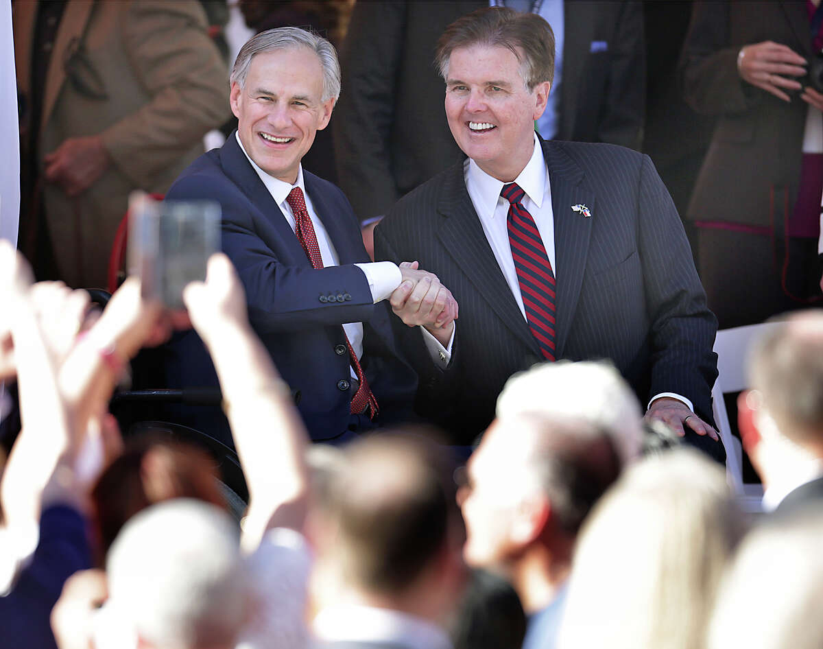 Texas Gov. Greg Abbott, left, and Lt. Gov. Dan Patrick shake hands for the crowd during the Inauguration Parade along Congress Avenue in Austin.