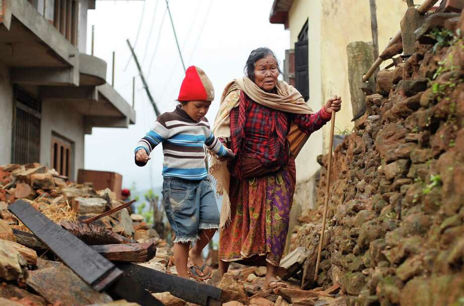 Sogat Rana, 7, leads his grandmother Jagot Kumari Rana, 79, through the rubble of homes in Paslang village near the epicenter of Saturday's earthquake. Photo: Wally Santana, STF / AP