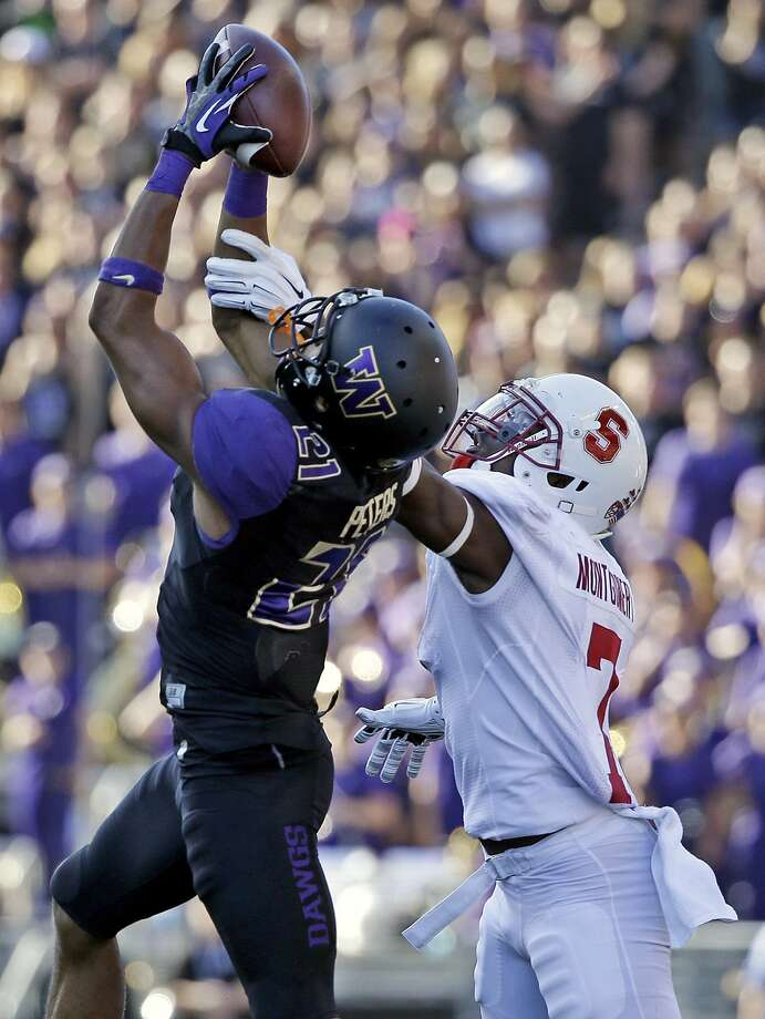 Washington cornerback Marcus Peters (left), who went to high school at McClymonds-Oakland, intercepts a pass against Stanford last September. Photo: Elaine Thompson, Associated Press