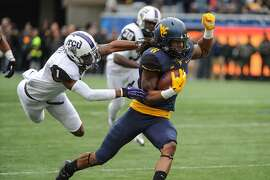 West Virginia's Kevin White (11) jukes past TCU defender Chris Hackett (1) during the first quarter of an NCAA college football game  in Morgantown, W.Va., Saturday, Nov. 1, 2014. (AP Phpto/Tyler Evert)