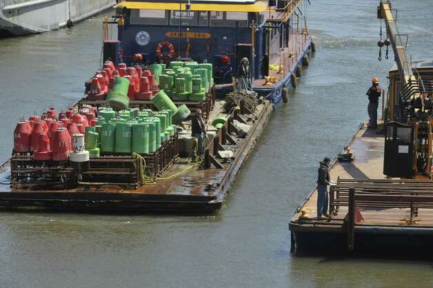 New York State Canal Corporation employees work on a barge with buoys on the Mohawk River as they set navigation buoys for the Erie Canal just below Lock 7 on Tuesday, April 28, 2015, in Niskayuna, N.Y.   Opening day of the canal system is scheduled for May 8th.   (Paul Buckowski / Times Union) Photo: PAUL BUCKOWSKI / 00031632A