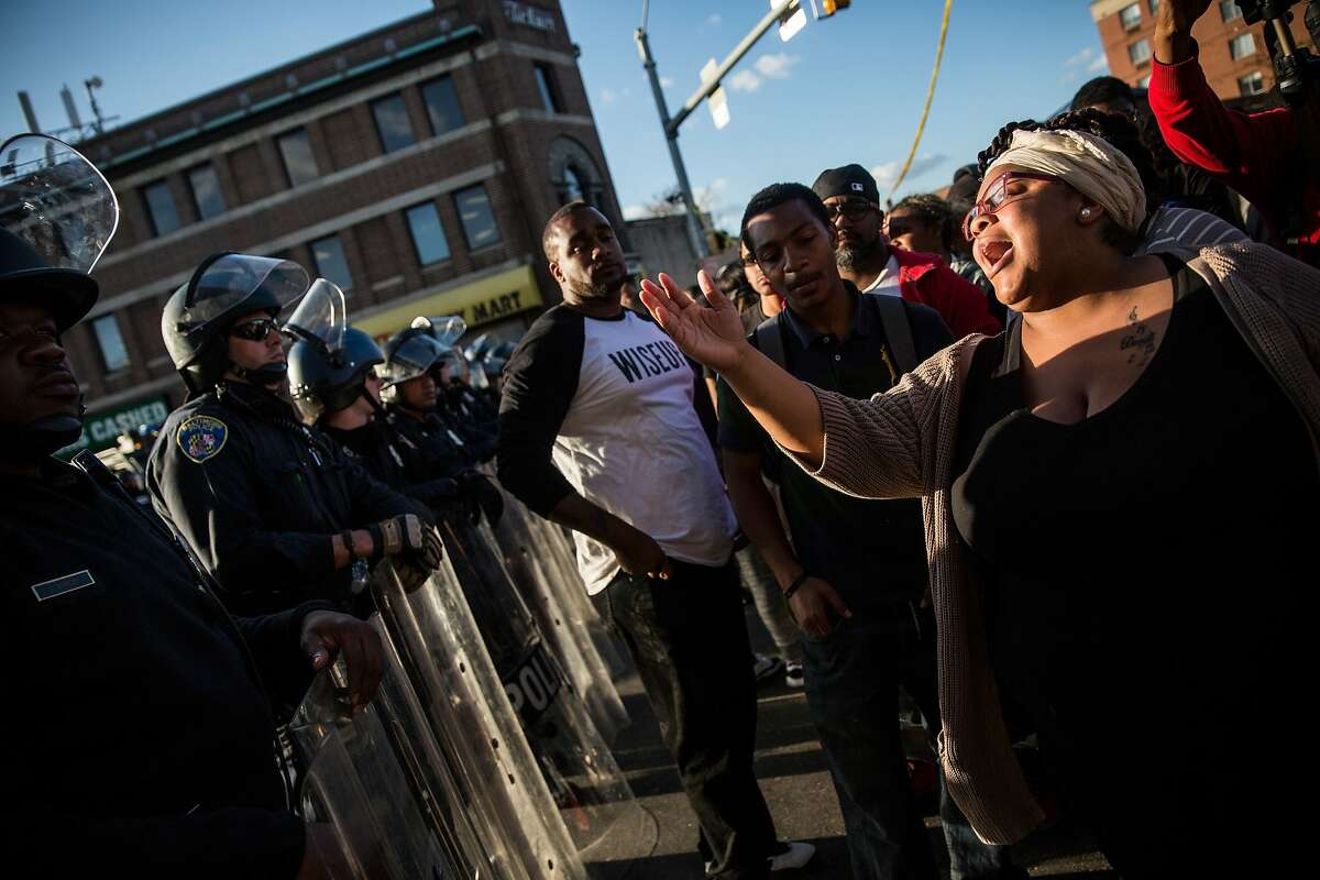 A woman yells at police near a CVS pharmacy that was set on fire Monday during rioting after the funeral of Freddie Gray who was injured while in police custody and died.