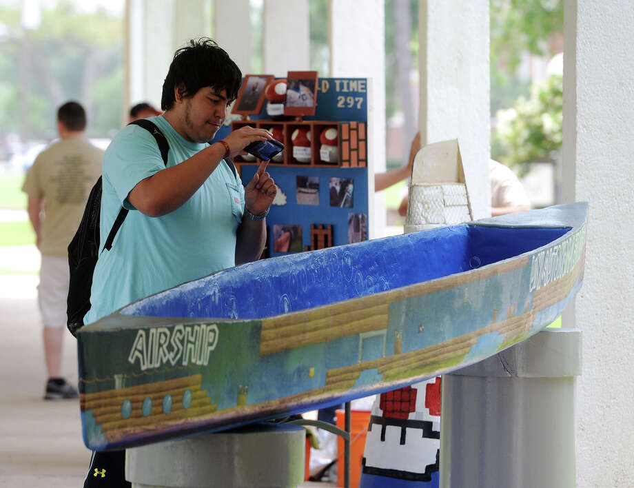 Jake Loredo stops to snap a picture of a canoe decorated in a Nintendo theme Friday. Competitors from 18 schools tested their concrete canoes Friday afternoon at Lamar University in preparation for Saturday's race. Photo taken Friday 4/24/15 Jake Daniels/The Enterprise Photo: Jake Daniels / ©2015 The Beaumont Enterprise/Jake Daniels
