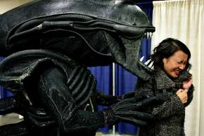 """Kristy Huynh recoils from Matthew O'Connor, who is dressed as the """"Alien,"""" at the WonderCon comic book convention in San Francisco on Saturday."""