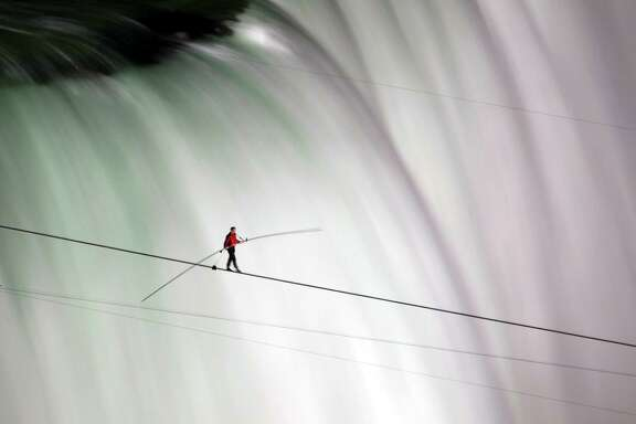 FILE -In this June 15, 2012 file photo, Nik Wallenda walks over Niagara Falls on a tightrope in Niagara Falls, Ontario. On Wednesday April 29, 2015, Wallenda will walk _ untethered _ atop the Orlando Eye, a 400-foot high Ferris wheel in Orlando, Fla., as it spins. (AP Photo/The Canadian Press, Frank Gunn, File)