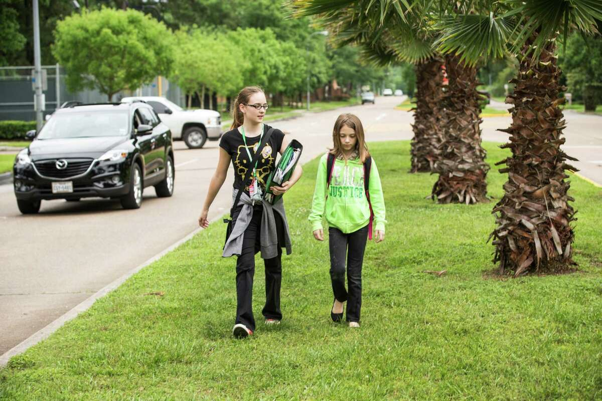 Amanda Nelson, 14, left, walks with her little sister, Savannah Stevens, 10, home from school on Friday, in Spring. There are few sidewalks on the sisters' route home and they are forced to walk on a median.