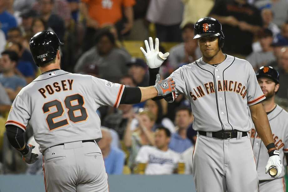 Justin Maxwell (right), congratulating Buster Posey on a homer Tuesday, is from  Maryland but said his family does not live near Baltimore and was not endangered by the civil unrest. Photo: Lisa Blumenfeld, Getty Images