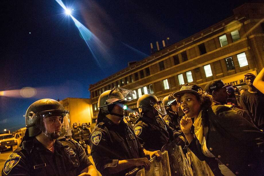 BALTIMORE, MD - APRIL 28:  A helicopter with a spot light watches over police and protesters before a mandatory, city-wide curfew of 10 p.m. near the CVS pharmacy that was set on fire yesterday during rioting after the funeral of Freddie Gray, on April 28, 2015 in Baltimore, Maryland. Gray, 25, was arrested for possessing a switch blade knife April 12 outside the Gilmor Houses housing project on Baltimore's west side. According to his attorney, Gray died a week later in the hospital from a severe spinal cord injury he received while in police custody.  (Photo by Andrew Burton/Getty Images) Photo: Andrew Burton, Getty Images