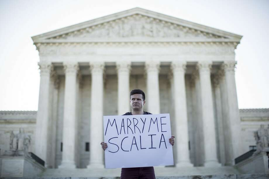 Same-sex marriage supporter Ryan Aquilina, of Washington, DC, holds a sign near the Supreme Court, April 28, 2015 in Washington, DC. On Tuesday the Supreme Court will hear arguments concerning whether same-sex marriage is a constitutional right, with decisions expected in June. Photo: Drew Angerer