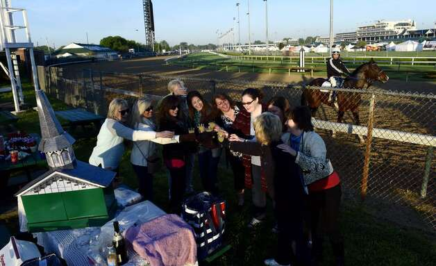 The annual party for the Downs Dames happened in the early morning Wednesday. They celebrated as horses trained on the track which hosts the 141st running of the Kentucky Derby on Saturday. (Skip Dickstein / Times Union)