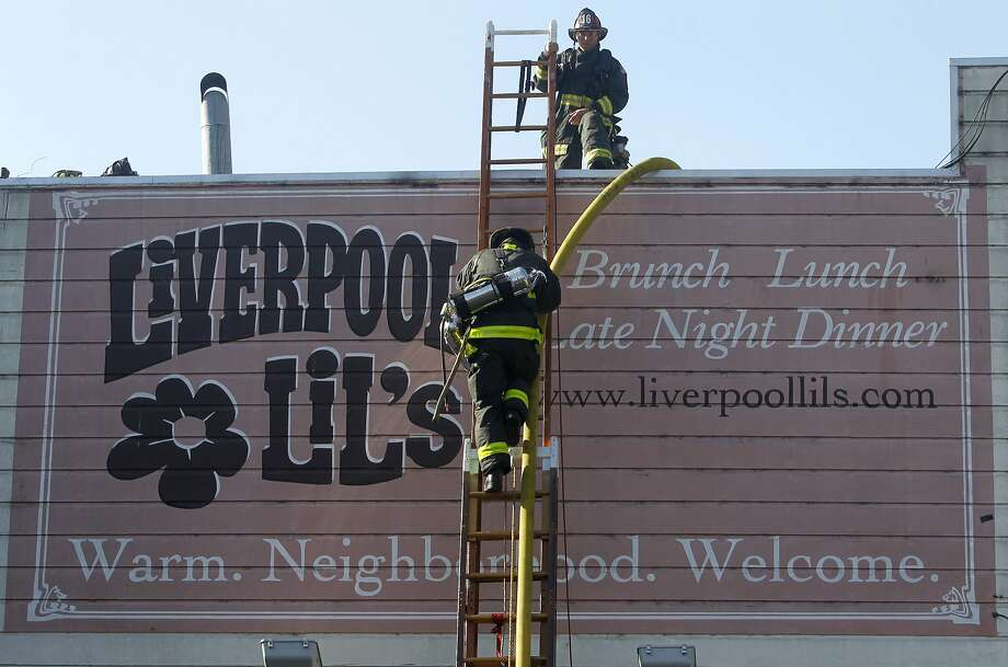 Firefighters climb down from the roof after extinguishing a two-alarm fire at Liverpool Lil's bar and restaurant on Lyon Street in San Francisco in 2015. Photo: Paul Chinn, The Chronicle