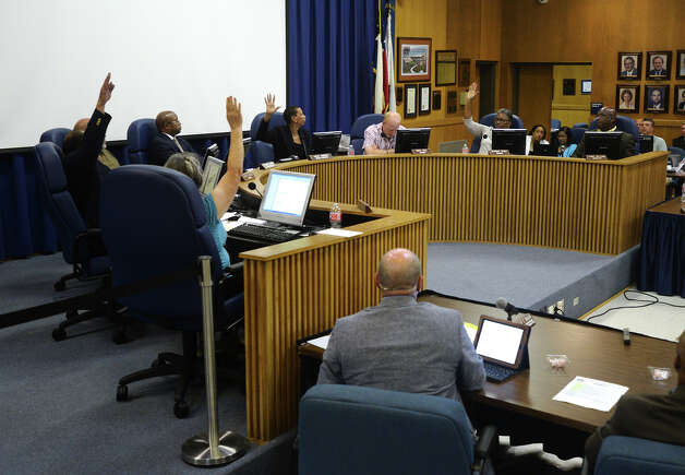 Trustees pass the reduction-in-force measures during Monday night's school board meeting. Janice Brassard, Woodrow Reece, Gwen Ambres, and Zenobia Bush voted for the measures, while Tom Neild and Mike Neil voted against, and Terry Williams abstained from the vote. The BISD school board voted Monday night to go forward with plans to slash more than 200 teaching positions across the district. Photo taken Monday 6/23/14 Jake Daniels/@JakeD_in_SETX Photo: Jake Daniels / ©2014 The Beaumont Enterprise/Jake Daniels