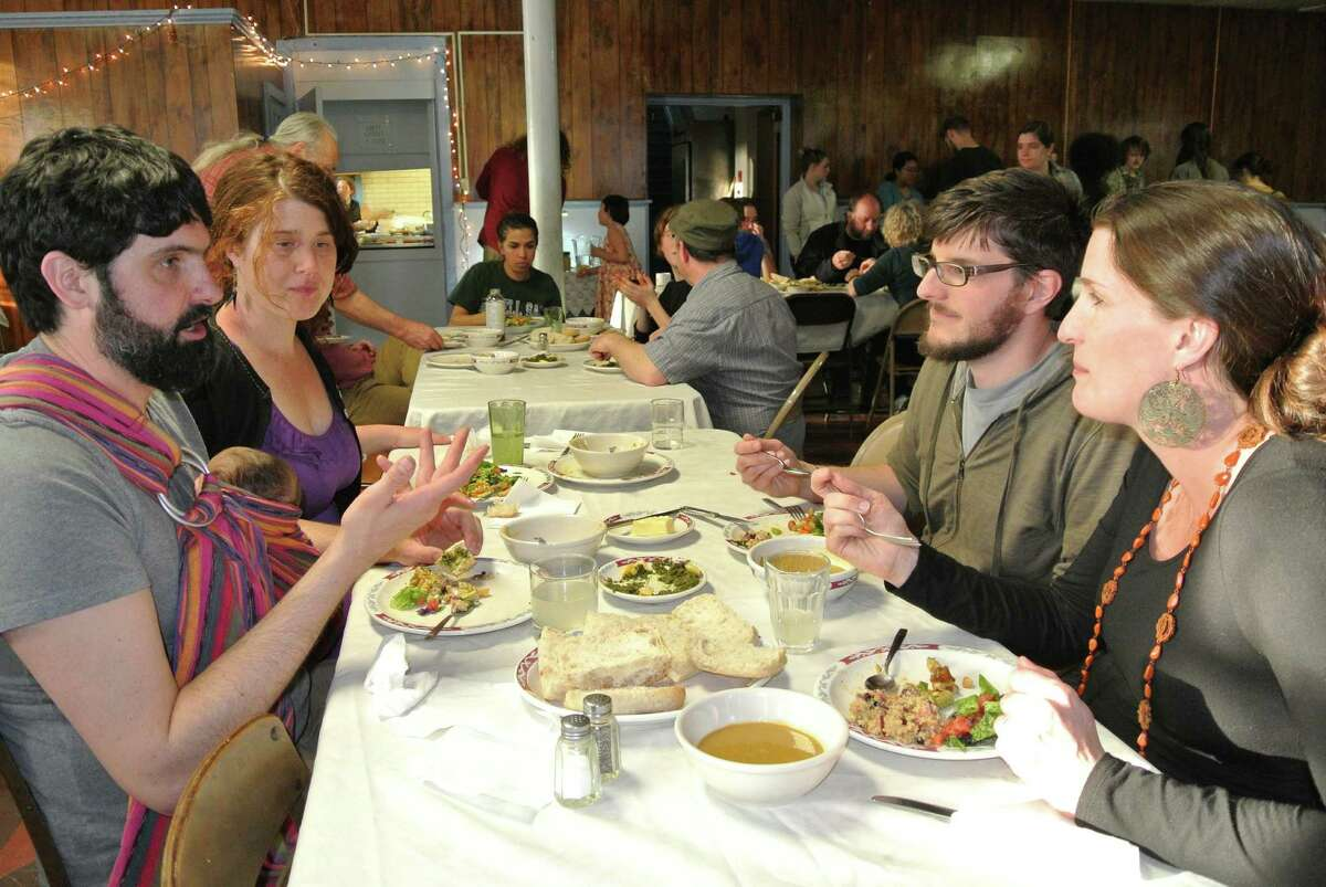 Jason Greco and Katie Nare, of Troy, dine with daughter Freya Nare Greco and converse with Jaron Kuppers and Sarah Parks, also of Troy, at Oakwood Soul Cafe at Oakwood Community Center, April 13, 2015. (Deanna Fox)