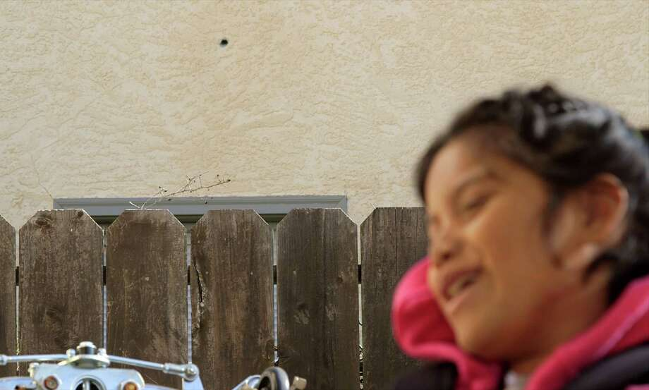 Jacqueline Funes, 9, on her front porch. A bullet hole can be seen in the wall behind her. Photo: Adam Grossberg/KQED / Adam Grossberg/KQED