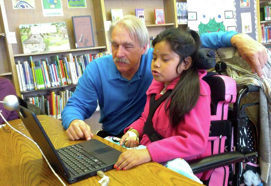 Chris Beatty, assistive technology professional for Oakland's schools, shows Jacqueline Funes how to operate a laptop with a sensor mounted on her forehead. Photo: Zaidee Stavely/KQED / Zaidee Stavely/KQED