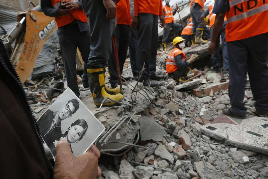 A relative holds an old photograph showing a family patriarch and his late wife found in the rubble. Photo: Manish Swarup, Associated Press