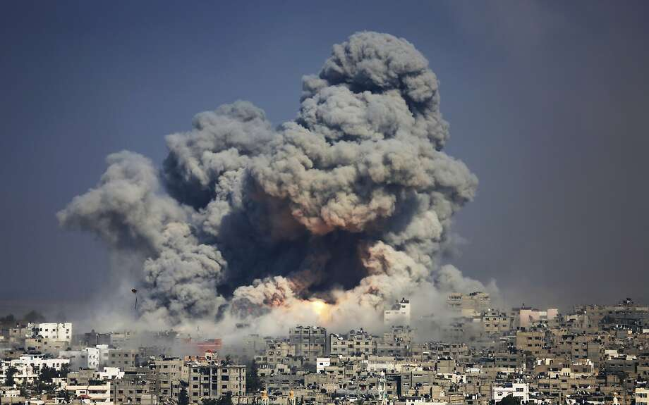 """FILE - In this July 29, 2014 file photo, smoke and fire from an Israeli strike rise over Gaza City. The conflict in Gaza placed sixth on Facebook's list of most popular topics worldwide in 2014, based on the number of posts, comments, likes, photos and videos shared. """"State of the News Media 2015,"""" published Wednesday, April 29, 2015, by the Pew Research Center's Journalism Project found that nearly half of Web users learn about politics and government from Facebook, roughly the same percentage as those who seek the news through local television and double those who visit Yahoo or Google News. (AP Photo/Hatem Moussa, File) Photo: Hatem Moussa, Associated Press"""
