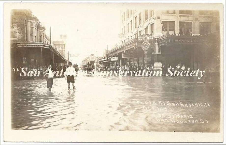 Flood at Saint Mary's and Houston Streets, looking west. The Gunter Building is on the right, with the Hertzberg Clock in front. People line the sidewalks of the buildings. Photo: Courtesy Of San Antonio Conservation Society Foundation