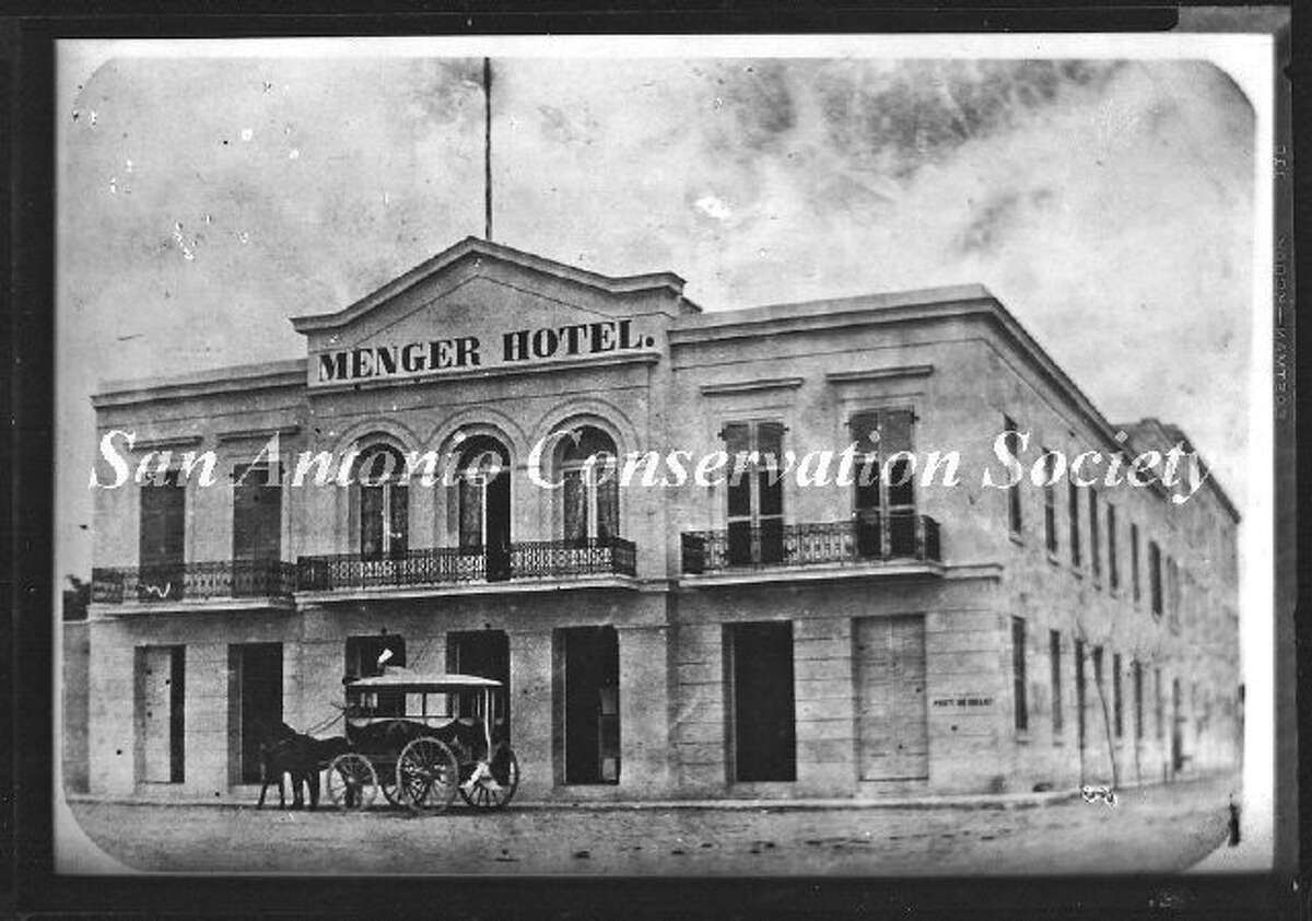 Copy print of an oblique view of the west and south facades of the original Menger Hotel. A horse drawn carriage stands in front of the Alamo Street entrance. Blum Street intersects to the south (at right).