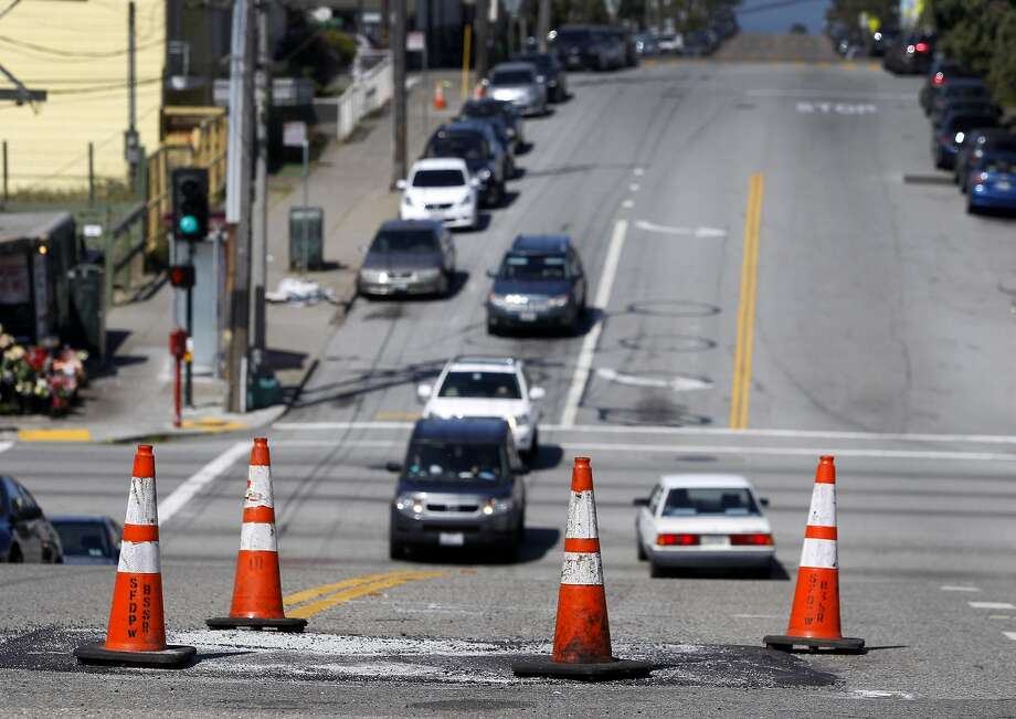 Traffic cones mark a persistent sinkhole on Quintara Street between 18th and 19th avenues in San Francisco, Calif. on Wednesday, April 29, 2015. City crews have filled the hole a number of times in the past two weeks and residents are hoping a permanent fix will be coming soon. Photo: Paul Chinn, The Chronicle