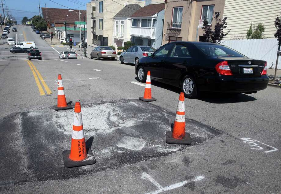 Drivers traveling on Quintara Street have to steer clear of a persistent sinkhole between 18th and 19th avenues in San Francisco, Calif. on Wednesday, April 29, 2015. City crews have filled the hole a number of times in the past two weeks and residents are hoping a permanent fix will be coming soon. Photo: Paul Chinn / The Chronicle / ONLINE_YES