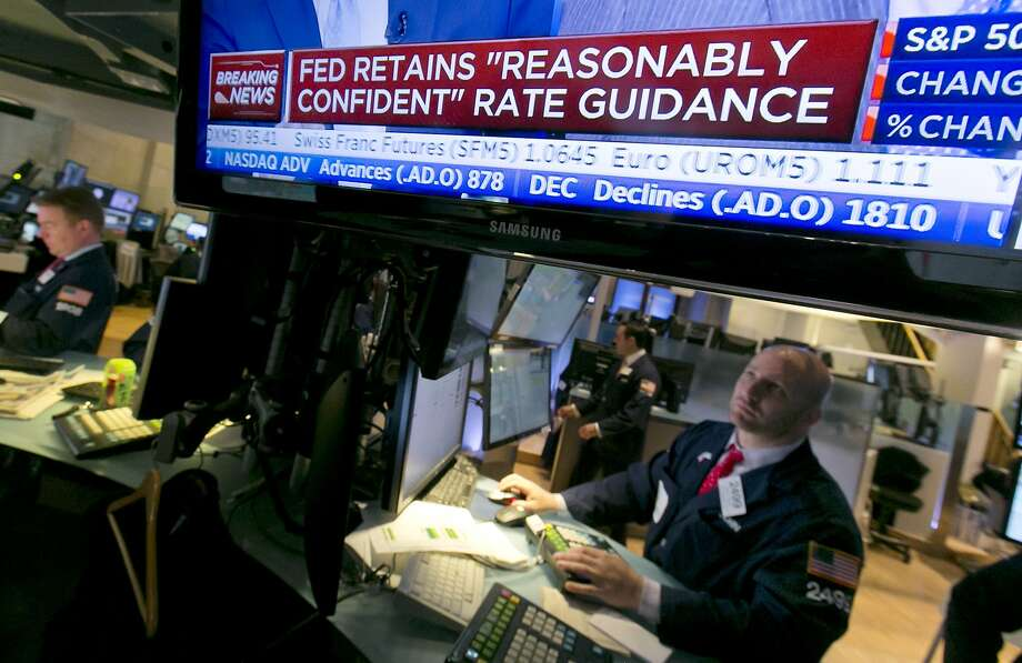 Specialist John Parisi, left, looks toward a television screen that shows the decision of the Federal Reserve, on the floor of the New York Stock Exchange, Wednesday, April 29, 2015. The Federal Reserve has downgraded its assessment of the economy after a winter in which growth nearly stopped. The Fed offered no sign that a rate increase might be coming soon. (AP Photo/Richard Drew) Photo: Richard Drew, Associated Press