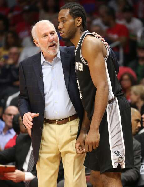 LOS ANGELES, CA - APRIL 28:  Head coach Gregg Popovich and Kawhi Leonard #2 of the San Antonio Spurs confer as they play the Los Angeles Clippers during Game Five of the Western Conference quarterfinals of the 2015 NBA Playoffs at Staples Center on April 28, 2015 in Los Angeles, California.  The Spurs won 111-107.  NOTE TO USER: User expressly acknowledges and agrees that, by downloading and or using this photograph, User is consenting to the terms and conditions of the Getty Images License Agreement.  (Photo by Stephen Dunn/Getty Images) Photo: Getty Images