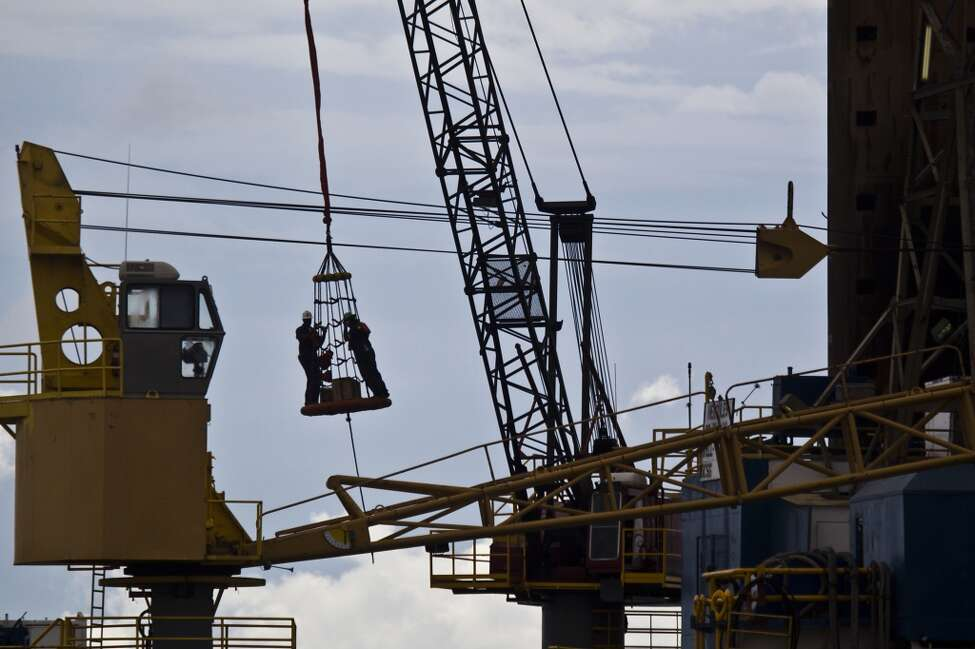 As a group of workers is lowered to a work boat to assist the loading of supplies on the Hercules 251, a shallow water drilling rig owned by Hercules Offshore on Wednesday, Aug. 11, 2010, near Port Fourchon. While shallow offshore drilling is not subject to a federal moratorium, Hercules officials say only two permits have been issued since June, idling activity in their fleet. The company has about 250 employees on idle rigs, with each rig costing the company about $25,000 per day to operate while generating no revenue for the company. ( Smiley N. Pool / Chronicle )