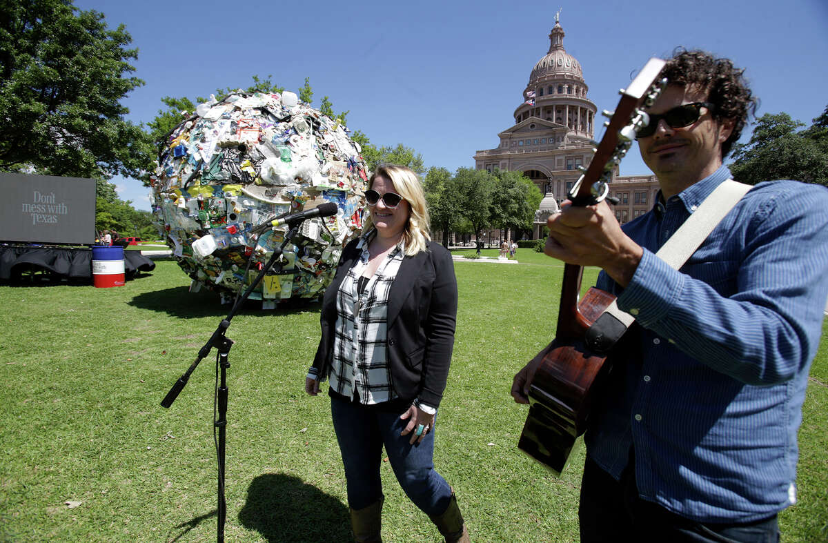 Emily Gimble, a singer from the band Asleep at the Wheel, performs after a 12 foot ball of trash is assembled on the south lawn of the State Capitol south lawn by TxDot to illustrate the problem of littering on Texas roads on April 29, 2015.
