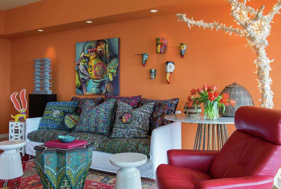 The living room is filled with art, including a teak tree wrapped with lights. Tandy had the sofa cushions and pillows handmade using Guatemalan huipil fabric. Photo: Michael Hunter