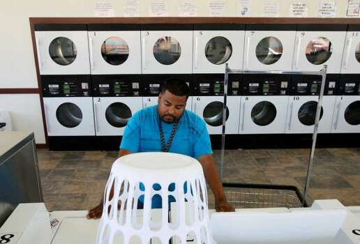 Jorge Castillo, 24, of San Juan, Texas, gets his laundry done at a laundromat in Carrizo Springs, Texas, Wednesday, March 28, 2012. The Rio Grande Valley resident took a job on a roustabout crew. The job is one of the lowest in the oil business and entails digging trenches, washing pits and moving rigs. Together with roommate and fellow worker, Juan Garcia, they earn $13 an hour and each pay $400 a month for a FEMA trailer in Asherton, Texas. But when there is no work, there is no money. The only jobs in the Valley available to Castillo would pay the minimum wage. Jerry Lara/San Antonio Express-News