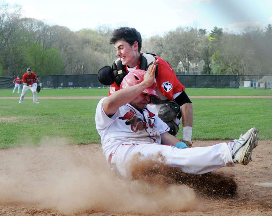 Fairfield Warde catcher John Natoli, left, puts the tag on Greenwich runner Jason Capozza, lower right, for an out at the plate during the bottom of the third inning of the high school baseball game between Greenwich High School and Fairfield Warde High School at Greenwich, Conn., Wednesday, April 29, 2015. Photo: Bob Luckey / Greenwich Time