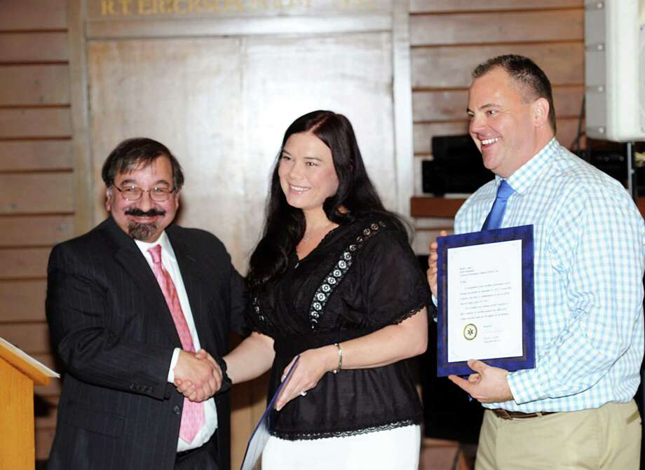 GEMS Deputy Director Art Romano, left, congratulates GEMS emergency medical personnel, Danielle Runyon, center, and Rob Camp, who were both instrumental in saving the life of a head trauma victim who crashed his bicycle while riding in the Montgomery Pinetum in Sept. of 2014, during the Greenwich EMS annual awards ceremony honoring volunteers & staff at the Greenwich Boat & Yacht Club, Greenwich, Conn., Wednesday, April 29, 2015. Photo: Bob Luckey / Greenwich Time