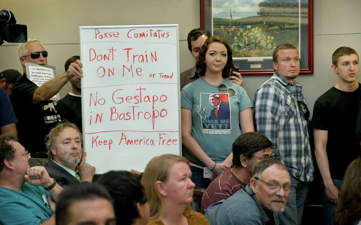 Bob Welch, standing at left, and Jim Dillon display a sign at a public hearing on April 27 in Bastrop about the Jade Helm 15 military training exercise.