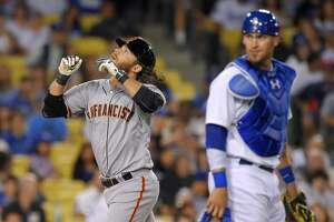 San Francisco Giants' Brandon Crawford, left, points to the sky while crossing home as Los Angeles Dodgers catcher Yasmani Grandal watches after hitting a two-run home run during the fourth inning of a baseball game, Wednesday, April 29, 2015, in Los Angeles. (AP Photo/Mark J. Terrill)